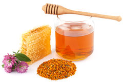 Honey in jar with dipper, honeycomb, pollen and flowers. Honey in glass jar with wooden dipper, honeycomb, pollen granules and clover flowers on white isolated Stock Photos