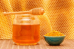 Honey in jar with dipper, honeycomb and pollen in. Honey in glass jar with wooden dipper and pollen granules in green porcelain bowl on light rustic mat with stock photo