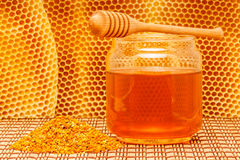 Honey in jar with dipper, honeycomb and pollen. Honey in glass jar with wooden dipper and pollen granules on light rustic mat with honeycomb background Stock Photo