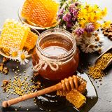 Honey jar and dipper. With leaking honey stock photos
