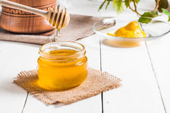Honey jar with dipper and lemon flowing, wood background Stock Photo