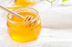 Honey jar with dipper and lemon flowing, wood background Stock Image