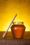 Honey jar with dipper on table Stock Images