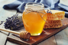 Honey in jar. With honey dipper on vintage wooden background Royalty Free Stock Images