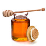 Honey jar and dripper. Honey in a glass jar with wooden dripper on top Royalty Free Stock Photos