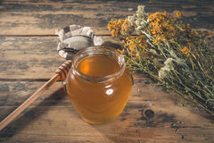 Honey jar and drizzle on wooden table Royalty Free Stock Photography