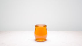 Honey jar, filled to brim, with copy space on either sides. A jar of honey filled to the brim, centered on a white marble counter, with copy space on both sides Royalty Free Stock Photos