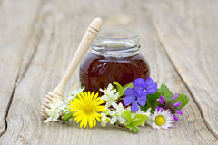 Honey in a jar and flowers Royalty Free Stock Image