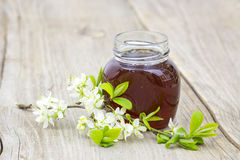Honey in jar and flowers stock photo