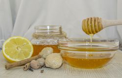 Honey and spices on a wooden surface. Honey in a jar and in a glass bowl with a wooden dipper on a wooden base, next to lemon, ginger,muscat walnut, cinnamon and Royalty Free Stock Images