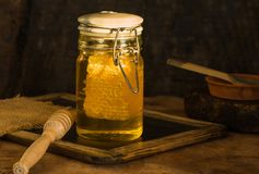 Honey with honey comb in a jar. Honey in a jar with honey comb inside Stock Photography