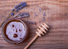 Honey in a jar, honey spoon and lavender flowers on the wooden t Stock Images