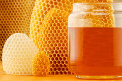 Honey in jar with honeycomb. Honey in glass jar, with honeycomb background on wooden rustic tabletop Royalty Free Stock Photography