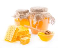 Honey in a jar and honeycomb. Jars with fresh flower honey and honeycombs on a white background Stock Photos