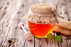 Honey in jar with honeycomb and wooden drizzler Royalty Free Stock Image