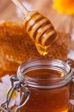 Honey in jar with honeycomb and wooden drizzler Stock Image