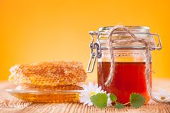 Honey in jar with honeycomb and wooden drizzler Royalty Free Stock Photos