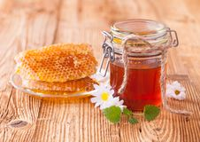 Honey in jar with honeycomb and wooden drizzler Stock Photo