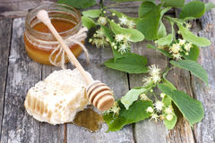 Honey in jar with honeycomb and wooden spoon Stock Image
