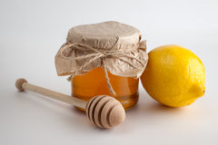 Honey in jar and lemon on a white background Stock Images