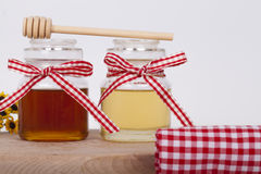 Honey in jar on a light background. Honey in  jar with honey dipper on a light background, selective focus and small depth of field Royalty Free Stock Images