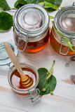 Honey in a jar and lime leaves stock photography