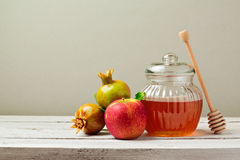 Honey jar, red apples and pomegranate on white wooden board Stock Photos