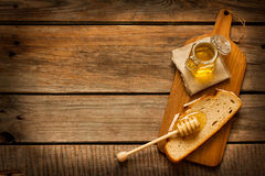 Honey in a jar, slice of bread and honey dipper on vintage wood. Honey in a jar, slice of bread and honey dipper on an old vintage planked wood table from above Stock Image