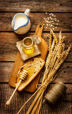 Honey in a jar, slice of bread, wheat and milk on vintage wood Royalty Free Stock Photos