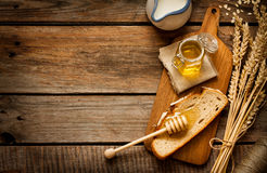 Honey in a jar, slice of bread, wheat and milk on vintage wood. Honey in a jar, slice of bread, wheat and milk on an old vintage planked wood table from above Stock Image