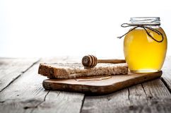 Honey in a jar, slice of bread, wheat on an old vintage planked wood table. Honey in a jar, slice of bread, wheat and milk on an old vintage planked wood table Royalty Free Stock Photo