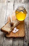 Honey in a jar, slice of bread, wheat on an old vintage planked wood table. Honey in a jar, slice of bread, wheat and milk on an old vintage planked wood table Stock Photo