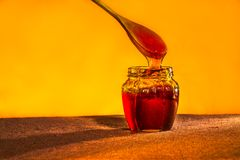 Honey jar with spoon and flowing honey,  canvas background Royalty Free Stock Photos