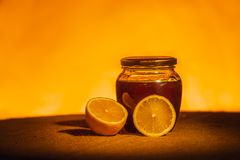 Honey jar with spoon and flowing honey,  canvas background Stock Photos