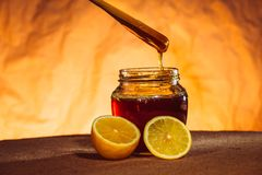 Honey jar with spoon and flowing honey,  canvas background Royalty Free Stock Images