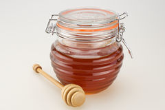 Honey. A jar of sweet flower honey with wooden drizzled stick Stock Photography