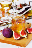 Honey in jar, white wine in glasses and ripe fig on wooden board Stock Photo