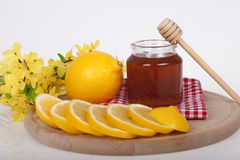 Honey in jar on a wooden background. Honey in  jar with honey dipper and lemon on a wooden background Royalty Free Stock Image