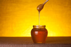 Honey jar with wooden dipper Stock Photos