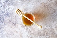 Honey jar with wooden spoon on grunge background royalty free stock image