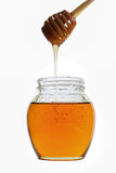 Honey. In jar with wooden spoon isolated on white background Royalty Free Stock Photography