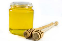 Honey jar and wooden stick.  Stock Image