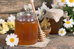Honey in a jar. On a wooden table royalty free stock images