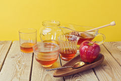 Honey jars and apple on wooden table. Stock Image