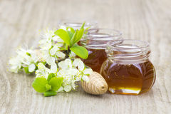 Honey in jars, flowers and honey dipper stock photo