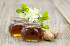Honey in jars, flowers and honey dippers royalty free stock photography