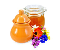 Honey in a jug and jar with flowers Stock Photo