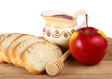 Honey in a jug and loaf apple on board Stock Images