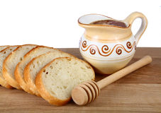 Honey in a jug and loaf on board Royalty Free Stock Photo