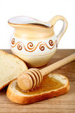 Honey in a jug and loaf on board Stock Photos
